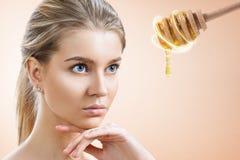 A colher da jovem mulher e do mel prepara-se para a m?scara facial fotos de stock