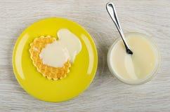 Colher de chá na bacia com leite condensado, cookie com leite em uns pires na tabela de madeira Vista superior fotografia de stock royalty free