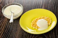 Colher de ch? na bacia com leite condensado, cookie com leite em uns pires na tabela de madeira fotografia de stock