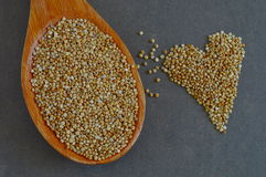 Colher de grões cruas do Quinoa e de grões na forma do coração Imagens de Stock