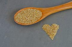 Colher de grões cruas do Quinoa e de grões na forma do coração Fotos de Stock