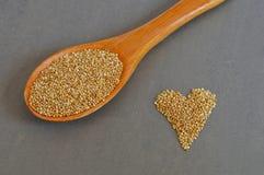 Colher de grões cruas do Quinoa e de grões na forma do coração Imagem de Stock Royalty Free