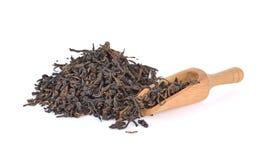Colher de madeira com chá preto com a folha no branco fotografia de stock royalty free