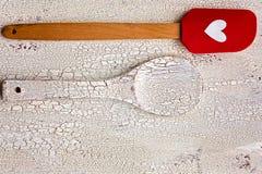 Colher de madeira da cozinha e espátula vermelha do silicone com coração na madeira Fotos de Stock