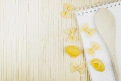 Colher de madeira e borboleta secada dos macarronetes em uma tabela de madeira fotos de stock