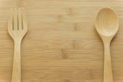 Colher de madeira e colher da forquilha no fundo de madeira Imagem de Stock
