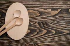 Colher de madeira e forquilha de madeira na placa de corte de madeira Foto de Stock