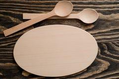 Colher de madeira e forquilha de madeira na placa de corte de madeira Imagem de Stock Royalty Free