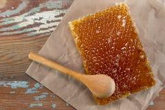 A colher de madeira inclina-se em Honey Comb Block imagens de stock