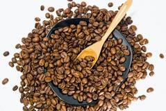Colher de madeira na bacia com feijões de café foto de stock royalty free