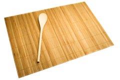 Colher de madeira na esteira do bambu Foto de Stock