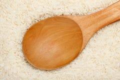 Colher de madeira no arroz perfumado tailandês do jasmim Fotos de Stock Royalty Free