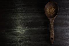 Colher de madeira no fundo de madeira preto da textura Imagem de Stock