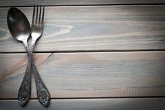 Colher de prata e forquilha do vintage em um fundo de madeira Utensílios da cozinha imagens de stock royalty free