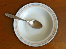 Colher de sopa na placa na tabela de madeira Imagens de Stock Royalty Free