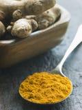 Colher do pó do Turmeric com raiz de Turmeric fresca Imagens de Stock