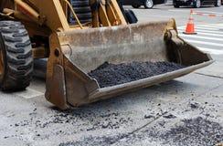 Colher do trator da foto no trabalho no pavimento de estrada Foto de Stock Royalty Free