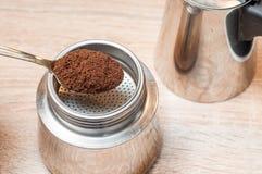A colher dourada derrama o café fabricado cerveja em um fabricante de café foto de stock