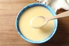 Colher e bacia de leite condensado na tabela, vista superior Produtos lácteos fotografia de stock