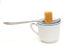 Colher e copo de açúcar de Brown Imagens de Stock Royalty Free