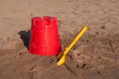 Colher e cubeta na areia Foto de Stock