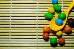 Colher e doces no fundo de madeira de bambu do teste padrão Fotos de Stock