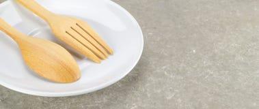 Colher e forquilha de madeira com prato branco Foto de Stock Royalty Free