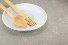 Colher e forquilha de madeira com prato branco Imagens de Stock