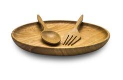 Colher e forquilha de madeira sobre o prato de madeira no isolado branco Foto de Stock Royalty Free