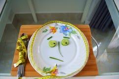 Colher e forquilha envolvidas em uma fita de medição e em vegetais em uma placa foto de stock royalty free