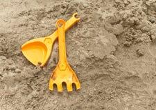 A colher e o raker da criança na areia Fotos de Stock