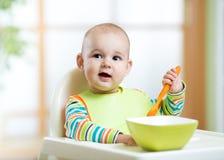 A colher infantil bonito feliz do bebê come-se Fotografia de Stock Royalty Free