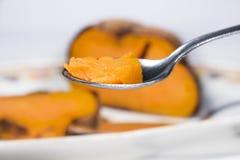 Colher na frente da bandeja cerâmica com a batata doce roasted Foto de Stock