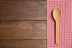 A colher na tabela de madeira com vermelho verificou a toalha de mesa Imagem de Stock Royalty Free