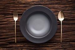 Colher vazia preta da forquilha da bacia no fundo de madeira da tabela Foto de Stock Royalty Free