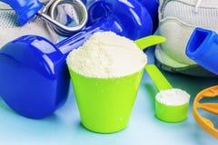 Colheres com proteína e creatina do soro com artigos do esporte ao redor Fotografia de Stock