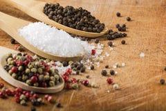 Colheres com sal e grãos de pimenta Foto de Stock