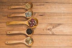 Colheres de madeira com as ervas diferentes para a infusão Imagens de Stock Royalty Free