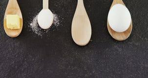 Colheres de madeira com ovo, cubo do queijo e açúcar pulverizado 4k filme