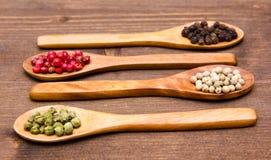 Colheres de madeira com pimentas misturadas na madeira Imagens de Stock Royalty Free