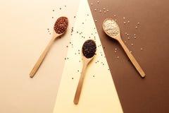 Colheres de madeira com tipos diferentes de quinoa e de espaço para o texto no fundo do ? imagens de stock