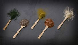 Colheres de madeira em um contexto da ardósia, com as pilhas das sementes e do suppl fotos de stock