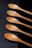 Colheres de madeira em uma placa da ardósia em um fundo preto Foto de Stock