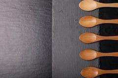 Colheres de madeira em uma placa da ardósia em um fundo preto Imagens de Stock