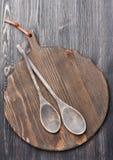 Colheres de madeira velhas da placa e do serviço de corte Imagens de Stock Royalty Free