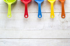 Colheres de medição coloridas para a cozinha em um backgrou de madeira branco Imagem de Stock