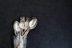 Colheres de prata e forquilhas no vidro Imagens de Stock Royalty Free
