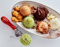 Colheres de sabores sortidos do gelado na bandeja imagem de stock