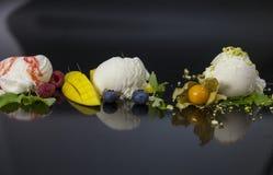 Colheres do gelado de baunilha com syrop, mirtilos, porcas e manga da morango Imagem de Stock Royalty Free