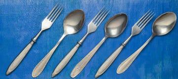 Colheres e forquilhas de aço em uma superfície de madeira azul Vista superior Fotos de Stock Royalty Free